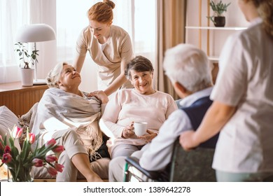 Young caregiver comforting elderly woman in nursing home