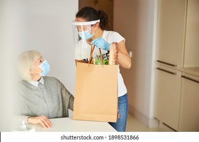 Junge Pflegeperson in einem Gesichtsschild, die einen Papierbeutel auf dem Küchentisch platziert