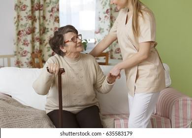 Young caregiver helping senior woman to stand up from the sofa