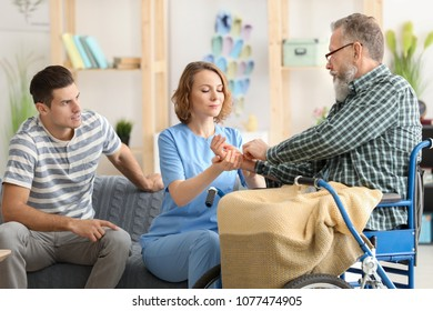 Young caregiver measuring pulse rate of senior man at home