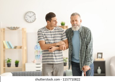 Young caregiver with senior man at home