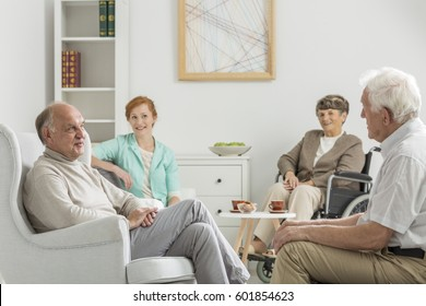 Young caregiver sitting with her elderly wards in nursing home