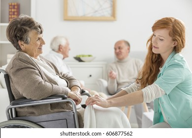 Young caregiver taking care of older disabled woman in nursing home