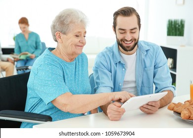 Young caregiver teaching senior woman to handle with tablet computer at home
