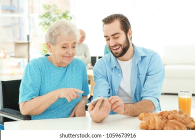 Young caregiver teaching senior woman to handle with mobile phone at home