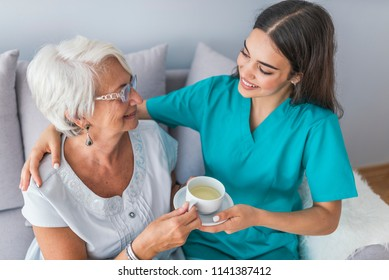 Young caregiver in uniform hugging smiling elderly woman during a home visit. Young helpful doctor taking care of senior woman in nursing home. Geriatric nurse and senior woman