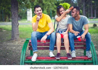 Young careless people are sitting on a bench in the park and having fun. Young and careless concept