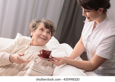 Young carer giving a cup to senior woman sitting on sofa.