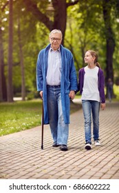 Young carer granddaughter walking in the park disabled senior grandfather