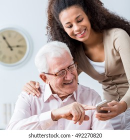 Young carer showing elderly happy man how to use smartphone