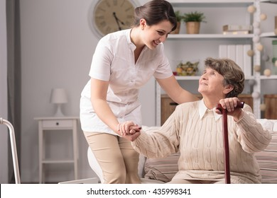 Young carer supporting senior disabled woman with walking stick.