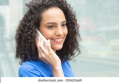 Young caribbean woman with curly hair listening at phone