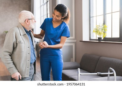 Young caring african nurse helping senior old elderly man grandfather walk . Disable old man trying to walk with the assistance aid of female doctor.