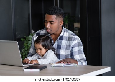 Young caring positive african-american father holding charming mixed race daughter in his arms pushing buttons of laptop while sitting at table with notebooks. Concept of combining business and family