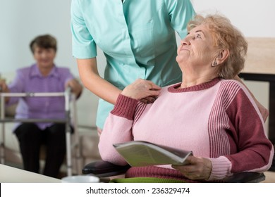 Young caring therpist and senior woman in nursing home
