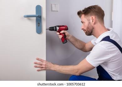 Young Carpenter Install Door Lock With Wireless Screwdriver