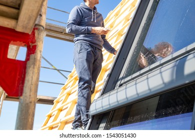 Young carpenter installing a skylight on a wooden roof truss
