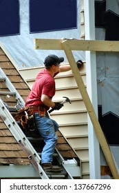 Young carpenter installs new siding on a two story home.  He is holding a hammer and nail.