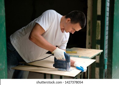 Young carpenter is sawing a plywood sheet with electric jig saw machine in carpentry workshop. Workwood DIY concept.
