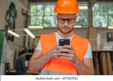 Young carpenter is using mobile phone at carpentry shop