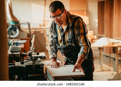 Young carpenter using power saw