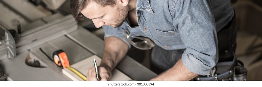 Young carpenter is using a tape measure