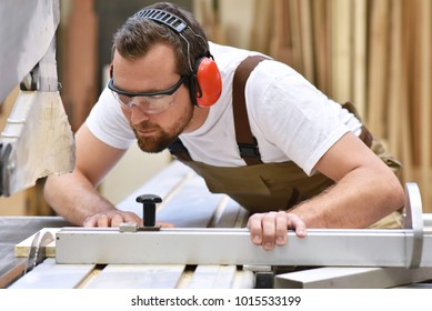 young carpenter in working clothes works in the joinery on a sanding machine - working clothes with goggles and ear protection