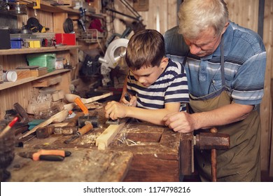 young carpenter working in a workshop. grandfather teaches grandson to work with a jack plane