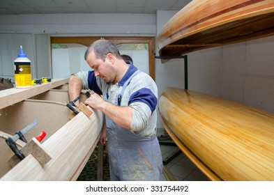 Young carpenters assembling new canoe of their own design.