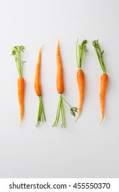 young carrots top view on white background, healthy food