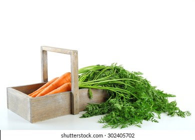 Young carrots in wooden box isolated on white