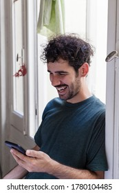 Young casual alternative model with moustache and curly hair using smartphone on a window indoors with natural light laughing with negative space.