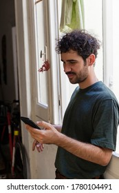 Young casual alternative model with moustache and curly hair using smartphone on a window indoors with natural light smiling facial expression and a corridor background with bike.