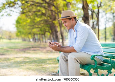 Young casual asian man using smartphone in park