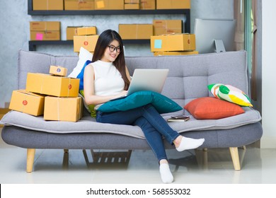 Young casual beautiful women entrepreneur, teenager business owner work at home, many stuff to do today in home. Sitting at sofa and using laptop