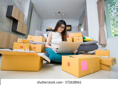 Young casual beautiful women entrepreneur, teenager business owner work at home, many stuff to do today in home. Sitting at floor and using laptop