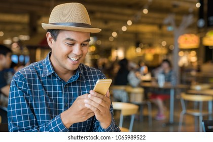 Young casual businessman using smartphone.