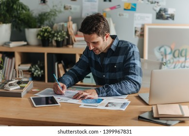 Young casual businessman writing at his office.