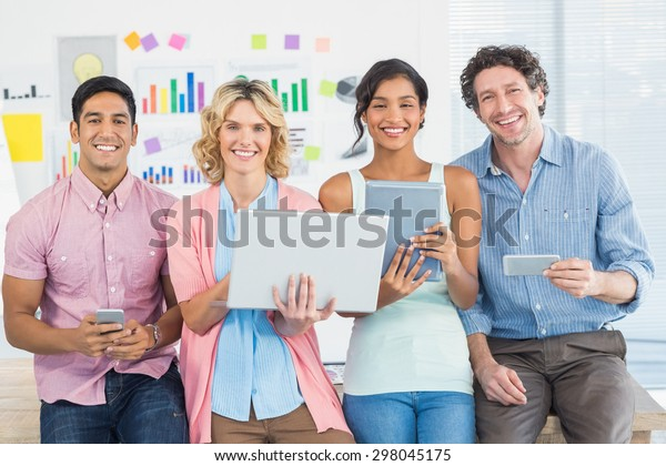 Young casual businesspeople using digital tablet with colleagues behind in the office
