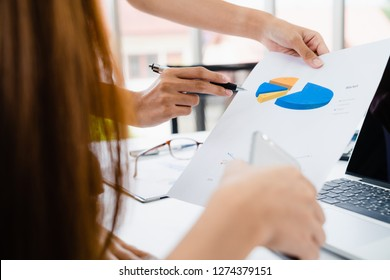Young casual businesswoman explaining business marketing plan detail on data paper to team in home office. Close up woman hands pointing pen at shart data sheet