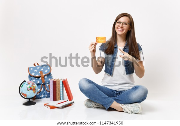 Young casual cheerful woman student in glasses pointing index finger on credit card sitting near globe backpack, school books isolated on white background. Education in high school university college