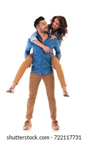 young casual couple looking at each other while man carrying woman on his back on white background