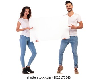 young casual couple pointing to a blank board on white background