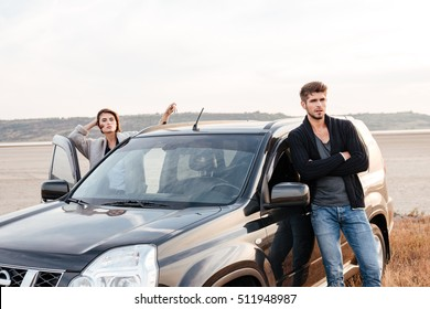 Young casual couple standing at their car on the seaside