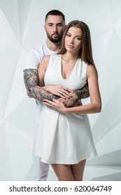 Young casual couple with woman holding his hands over woman's shoulder and looking for the camera. On white background