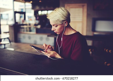 Young casual dressed female watching training webinar on her touchpad using internet connection. Caucasian student girl searching video in network wearing white headphones