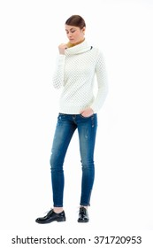 Young, casual, fashion, beautiful girl standing in a studio a sweater and jeans. Isolated on white background