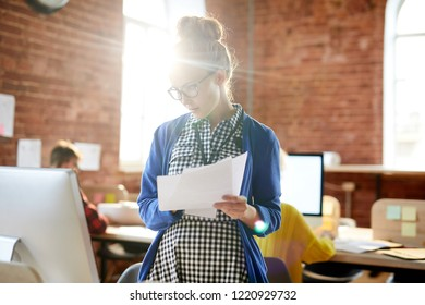 Young casual female economist with papers standing in front of computer monitor and reading online data