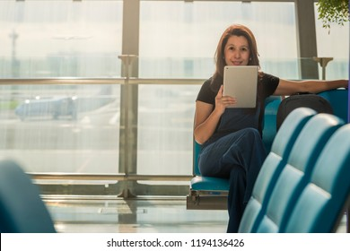 Young casual female traveler at airport, holding tablet device, sitting near the airport gate windows at planes on airport runway. Copy space