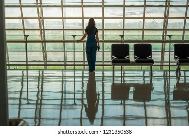Young casual female traveler at airport, holding smartphone device, standing near window, looking through the airport gate windows at planes on airport runway before boarding. Copy space